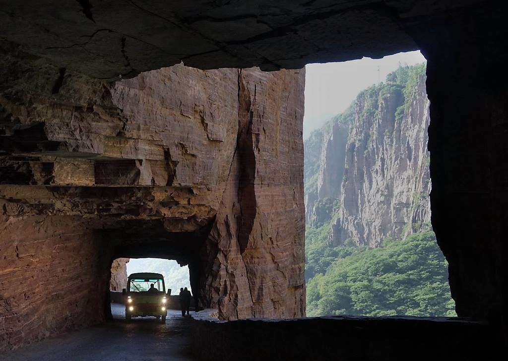 (170515) -- ZHENGZHOU, May 15, 2017 (Xinhua) -- A tour bus runs on the Guoliang cliff corridor in Guoliang Village, Huixian County, central China's Henan Province, May 13, 2017. The Guoliang cliff corridor is a 1,300-meter-long road built along the cliff of 1,000 meters high. The construction of this miraculous road lasted five years from 1972 to 1977, and was built purely by hand by villagers of Guoliang Village. (Xinhua/Li An) (wyo)